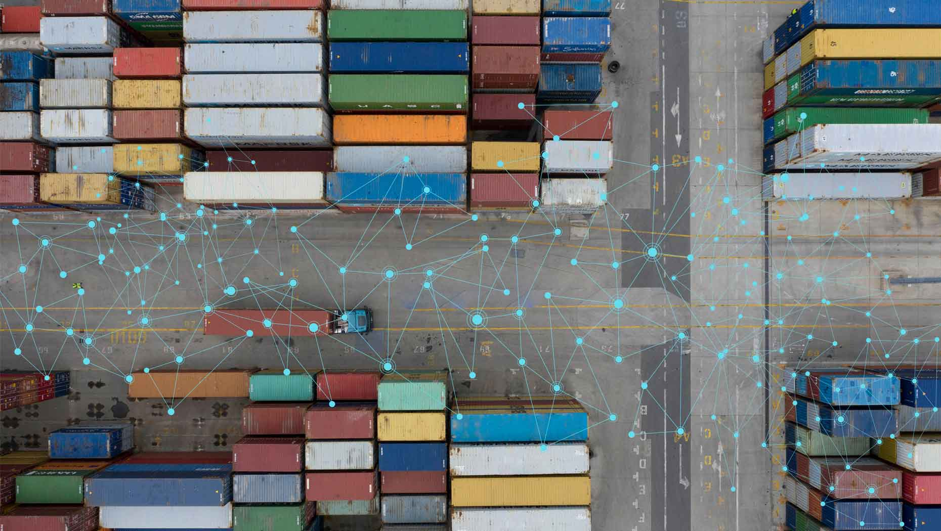 Aerial view of a Volvo truck driving between colourful cargo containers